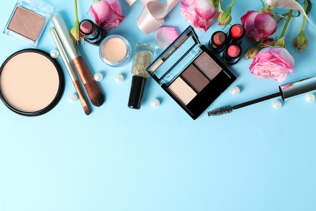 Different makeup cosmetics and flowers on blue background