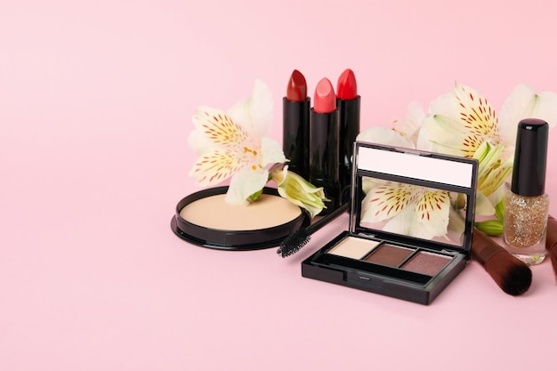 Different makeup cosmetics and flowers on pink background