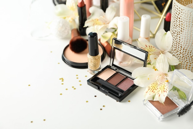 Different makeup cosmetics and flowers on white background