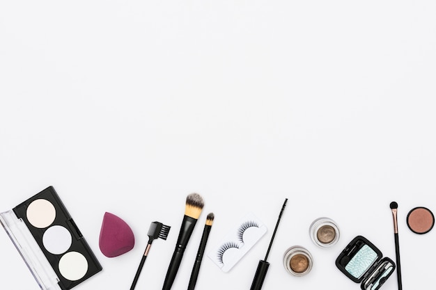 Different makeup cosmetics and makeup brushes on white background