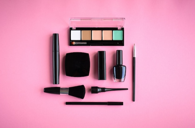 Different makeup products composition on pink background