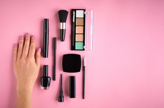 Different makeup products composition with hand on pink background