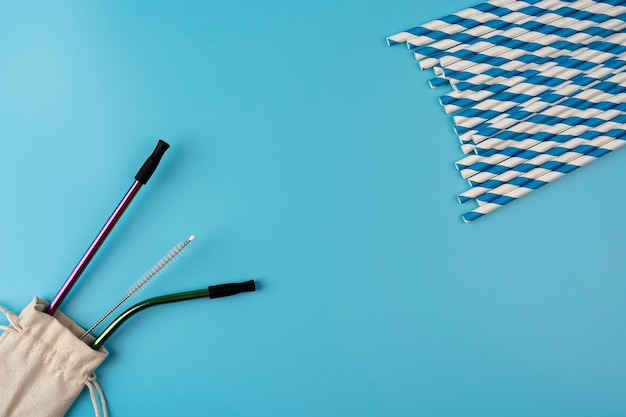 パステルブルーの背景紙と環境にやさしいプラスチックフリーのさまざまな素材のストロー
