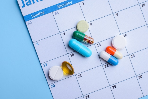 Different medical pills lay on calendar.