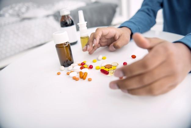 別の薬。白い表面に横たわっている丸薬に伸びるアフリカ系アメリカ人の男の子の手のクローズアップ