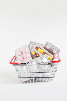 Different medicine blisters in the stainless steel basket on white background