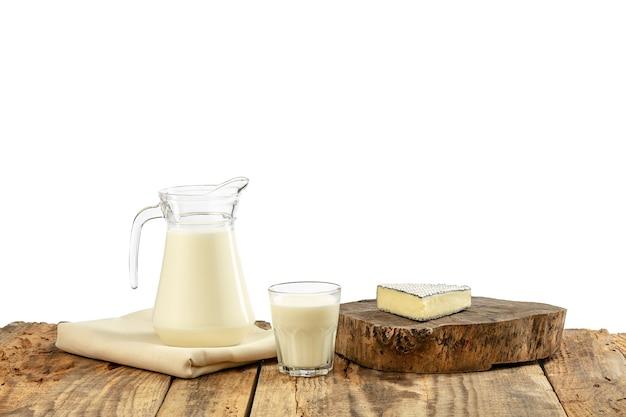 さまざまな乳製品、チーズ、クリーム、木製のテーブルと白い壁にミルク。健康的な食事とライフスタイル、有機的な自然栄養、食事。おいしい食べ物や飲み物。
