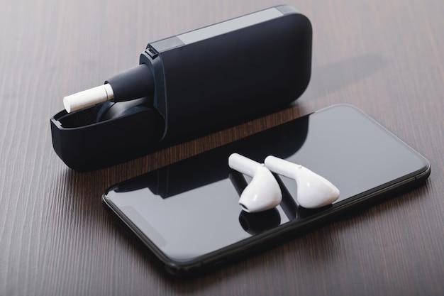 さまざまな最新の電子機器-タバコ加熱システム、ワイヤレスイヤホン、スマートフォン