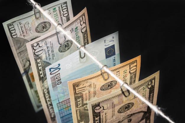 Different new dollar bills with twenty euro bill between them are hanging on dark