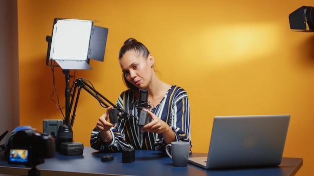 블로거 책상에 있는 다양한 np-f 스타일 배터리를 카메라로 가져갑니다. 온라인 인턴을 위한 전문 비디오 사진 장비를 말하는 소셜 미디어의 콘텐츠 제작자 뉴 미디어 스타 인플루언서