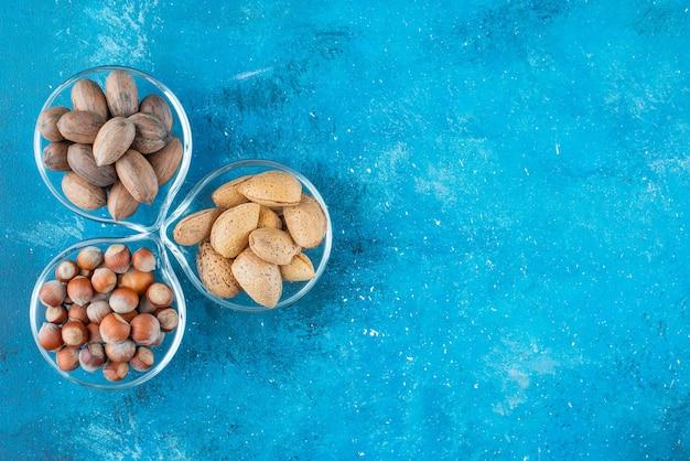 Diverse ciotole di noci, sul tavolo blu.