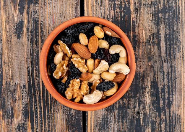 Различные орехи и изюм в коричневой миске на деревянном столе текстуры