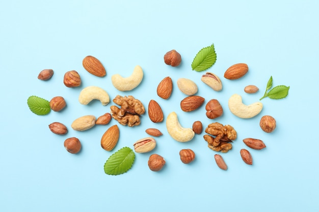Different nuts on blue background, top view. vitamin food