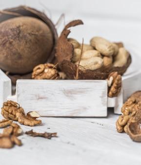 白い木製の背景に別のナッツのクローズアップ
