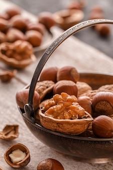 Different nuts on dark stone table. hazelnut, walnuts.