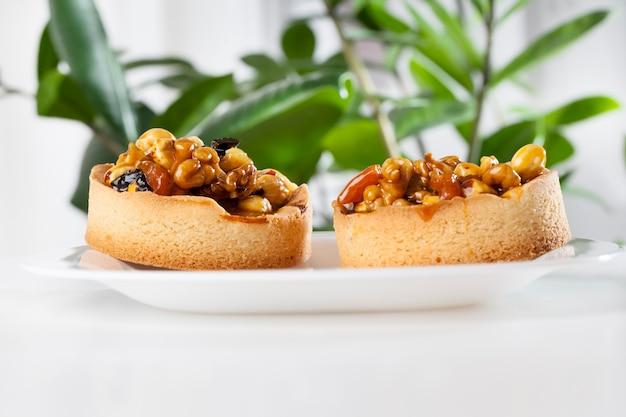 Различные орехи в круглой тарталетке, круглая тарталетка с орехами и сухофруктами, залитая карамелью, ингредиенты, используемые в приготовленной тарталетке: фундук, аразис, курага, сушеная слива, грецкий орех.