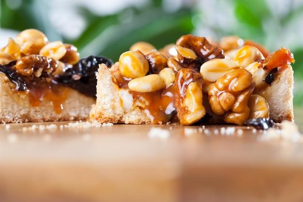 丸いタルトのさまざまなナッツ、ナッツとドライフルーツをキャラメルで注いだ丸いタルト、作られたタルトに使用される成分は、ヘーゼルナッツ、ピーナッツ、ドライアプリコット、プルーン、クルミです。