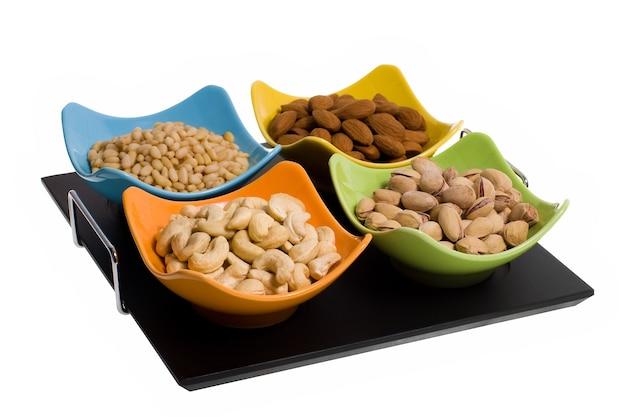 白で隔離されるカラフルな皿のさまざまなナッツ