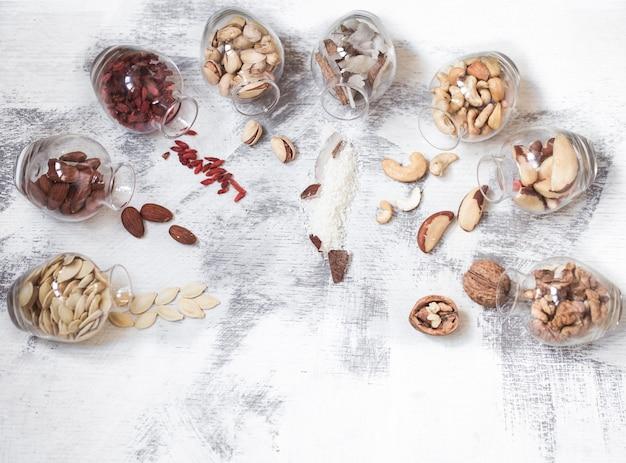 Различные орехи в баночках на светлом деревянном фоне, концепция здорового питания