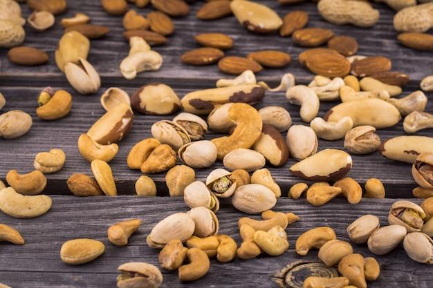 暗い背景の木の異なるナッツ