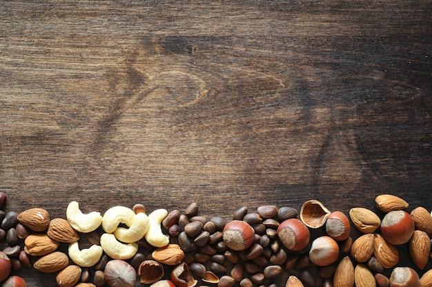 Различные орехи на деревянном столе. кедр, кешью, фундук, грецкие орехи и ложка на столе. многие орехи в скорлупе и чистченых на деревянном фоне.