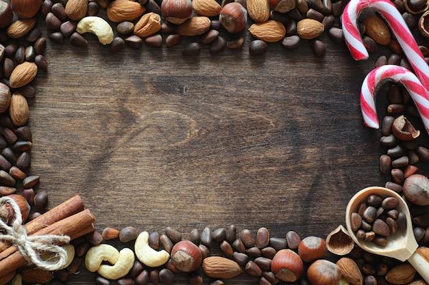나무 테이블에 다른 견과류입니다. 테이블에 삼나무, 캐슈, 헤이즐넛, 호두, 숟가락. 많은 견과류는 나무 배경에 껍질과 chistchenyh입니다