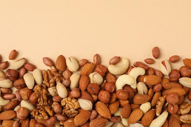 Различные орехи на бежевом фоне, вид сверху. витаминная пища