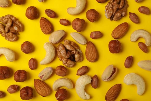 Различные орехи на желтом фоне. витаминная пища