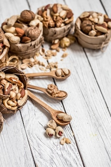 Different nuts in plates and wooden spoons closeup on white wooden background ,concept of healthy protein power