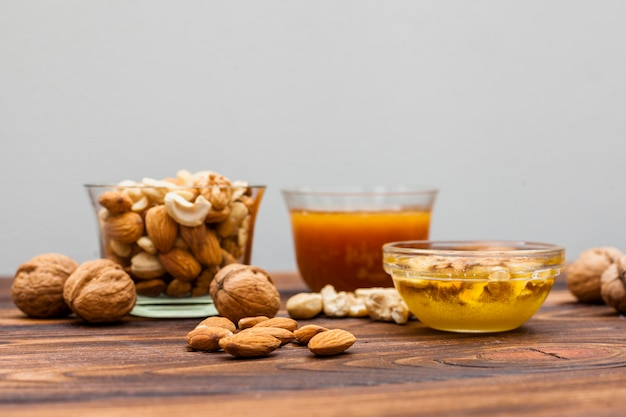Different nuts with honey in bowls on table
