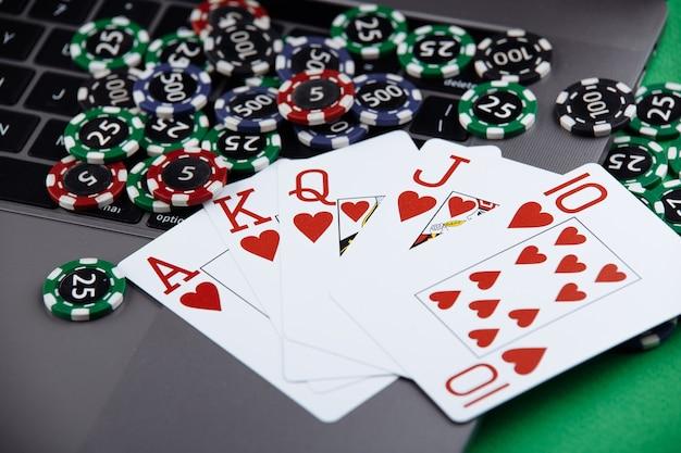 ラップトップでのカードの積み重ねとトランプのコストの異なるカジノチップ。ゲームに賭けて勝ちます。