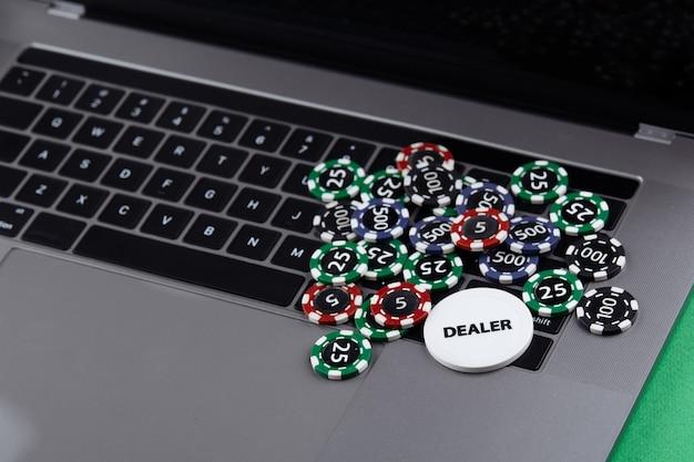 ラップトップにスタックするコストの異なるカジノチップ。ディーラー。ゲームに賭けて勝ちます。