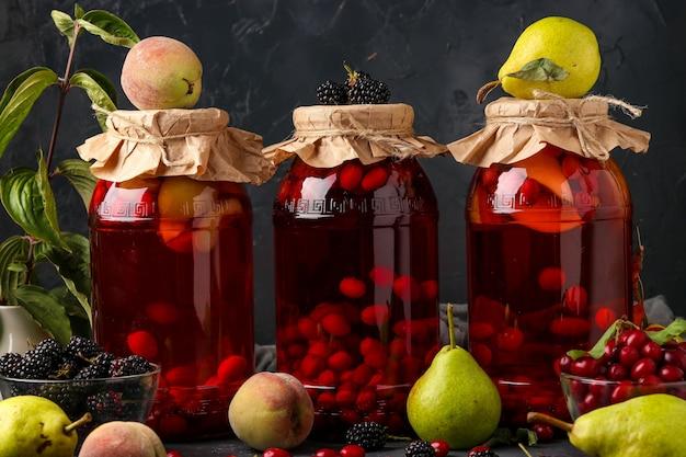 暗い表面、水平方向の瓶に桃、梨、ブラックベリーが入ったハナミズキのコンポートの違い
