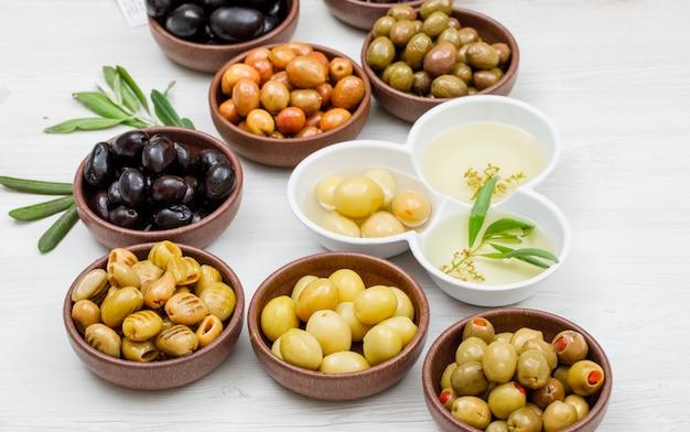 Olive e olio d'oliva differenti in un'argilla e ciotole bianche con la vista dell'angolo alto delle foglie di ulivo su legno bianco