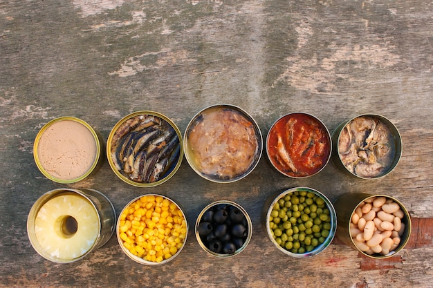 Different open canned food on old wooden background
