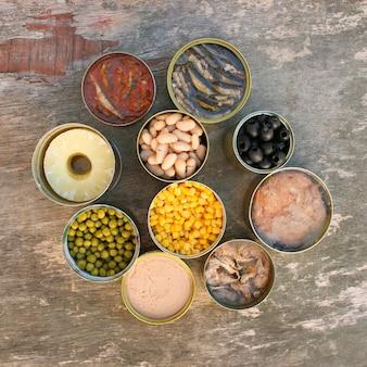 古い木製の背景にさまざまなオープン缶詰食品。上面図。フラットレイ。