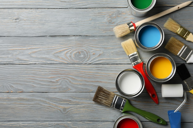 Different paints, brushes and roller on wooden surface