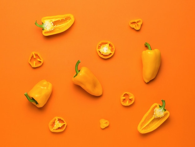 Different parts of bell pepper on a bright orange background. vegetarian food.