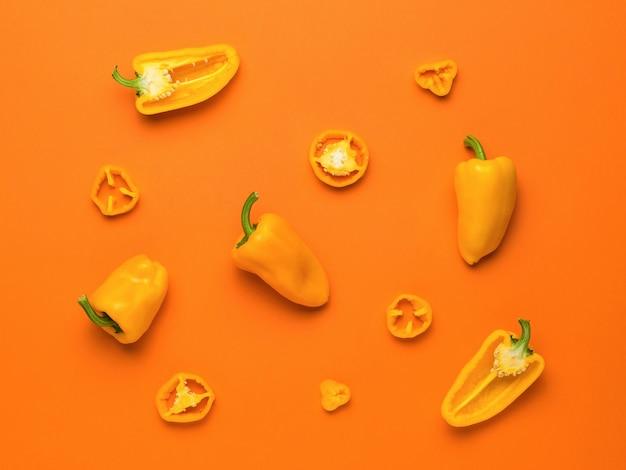 Различные части болгарского перца на ярко-оранжевом фоне. вегетарианская пища.