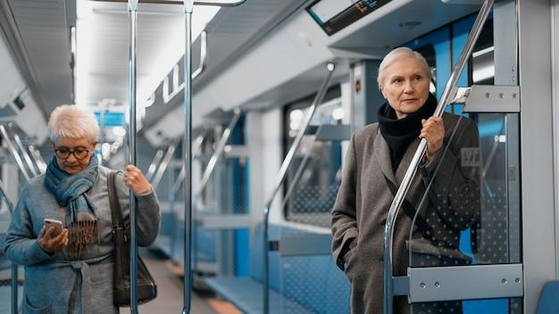 地下鉄車両の都会のライフスタイルのさまざまな乗客