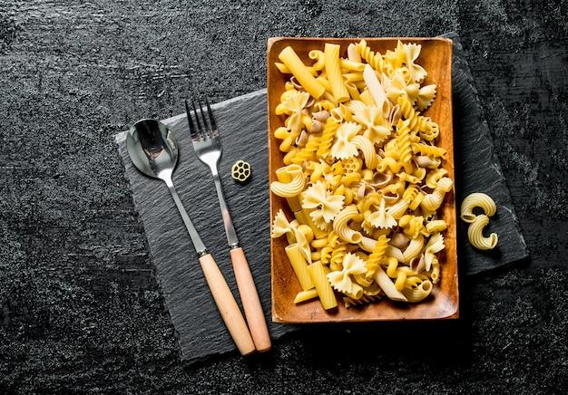 黒い木製のテーブルの上にフォークとスプーンで皿の上で乾いた別のパスタ