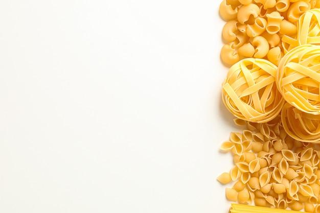 Различные макароны на белом фоне, пространство для текста. сухие сырые целые макароны