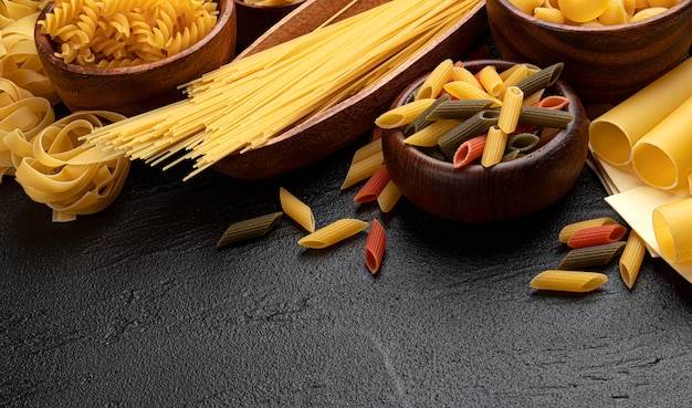 Different pasta types on black background with copy space for text