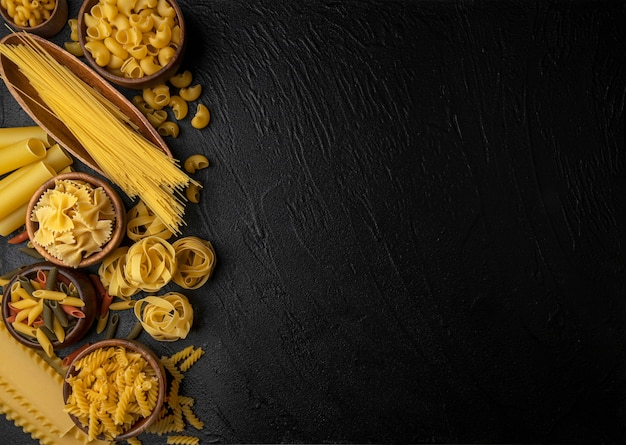 Different pasta types on black background with copy space, top view