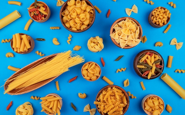 Different pasta types on blue background with copy space for text, flat lay composition of italian food ingredients concept, top view of dried mixed pasta pattern on color table