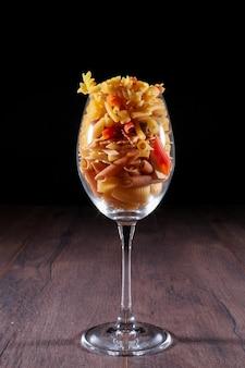 黒い表面にワイングラスの異なるパスタの種類