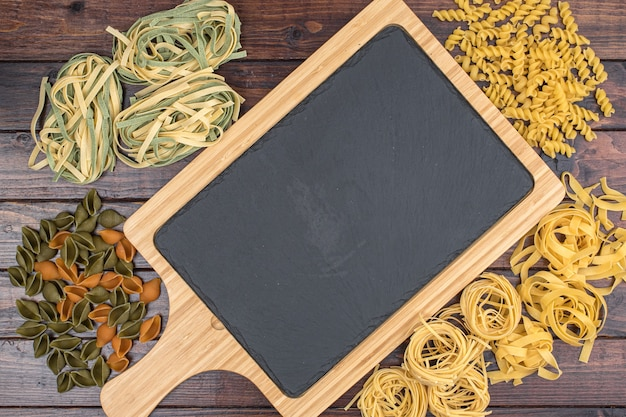 Different pasta with cutting board in the middle on dark background. flat lay. top view.