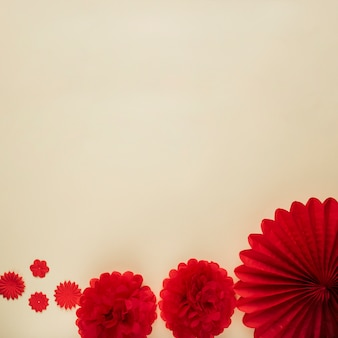 Different pattern of red origami flower cutout on beige background