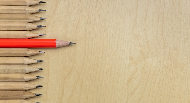 Different pencil standout show leadership concept. wooden background
