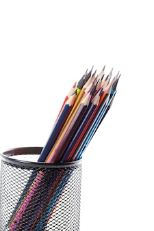 Different pencils colored graphite and drawing inside black basket on white wall